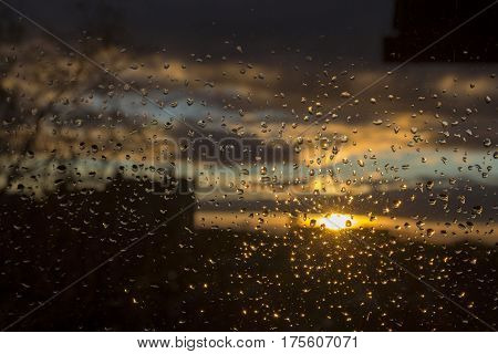Sunset City Through Rainy Window.  Raindrops On Glass Window Against Sky During Sunset.