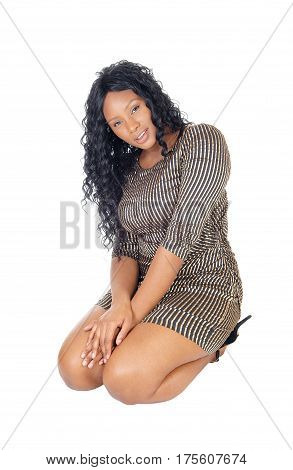 A beautiful African American woman in a short dress and long curly black hair kneeling isolated for white background.