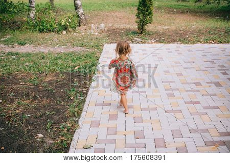 Curly Blond Child Playing Outdoors In Summer.
