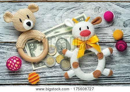 concept of starting forex traiding. small amount of money euro coins and us dollar banknotes and rattle knitted homemade toys for toddlers bulls and bears. education in foreign exchange trade.