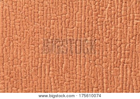 Orange fluffy background of soft fleecy cloth. Texture of textile closeup.