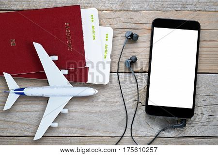 Plane tickets passports smartphone with earphones and toy plane on table