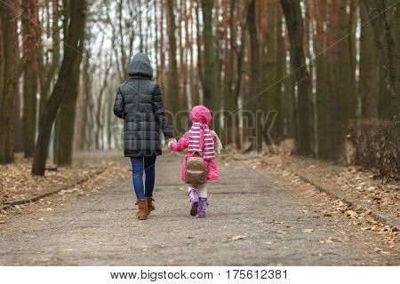 Happy mother and child daughter holding hands together walking in spring park