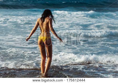 Pretty Girl In Sexy Yellow Swimsuit Walking In Wavy Sea