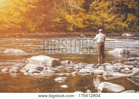 Unidentifiable fly fisherman on a river during fall