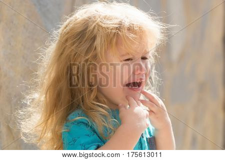 Cute unhappy baby boy with long blond hair in blue tshirt crying outdoors on sunny summer day on blurred grey wall background