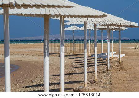 Umbrellas beach chairs tents on the beach in the sun when the dawn.