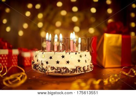 Happy birthday cake with candles on the background of garlands and letters.