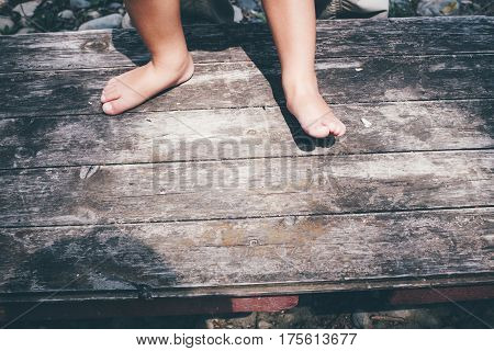 Little Girl Barefoot Closeup Of A Foot On A Plank Background.