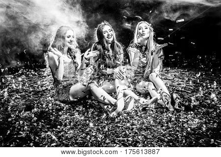 Black and white photo of three women sitting on the floor covered with confetti