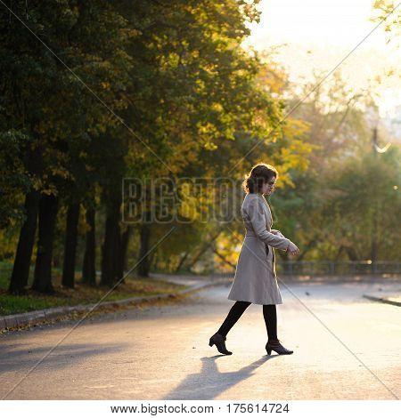 Slender brunette girl in beige coat crossing empty street at sunrise square