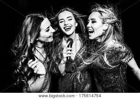 Black and white photo of three gorgeous women in festive dresses singing karaoke
