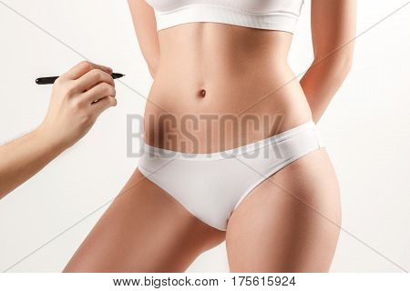The female hand drawing lines on woman's abdomen. Young, slim, healthy and beautiful woman in white lingerie isolated on the white background.