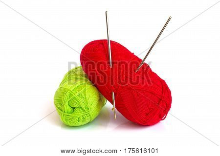 The photo shows two skeins of yarn. In a skein of yarn of red color hooks for knitting are stuck.
