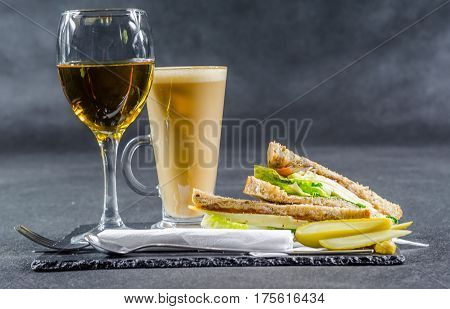 set consisting of two sandwiches malted bread with vintage cheddar cheese pickles red onion tomato lettuce white wine and coffee latte breakfast set