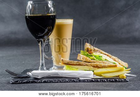 set consisting of two sandwiches malted bread with vintage cheddar cheese pickles red onion tomato lettuce red wine and coffee latte breakfast set