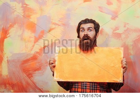 Surprised Bearded Man Holding Orange Oil Paint Texture On Canvas