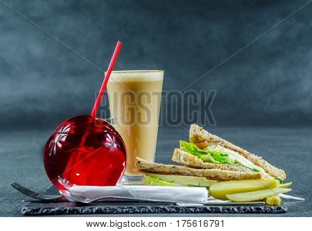 set consisting of two sandwiches malted bread with vintage cheddar cheese pickles red onion tomato lettuce drink and coffee latte breakfast set