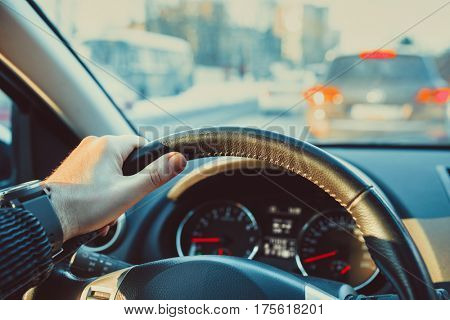 Car steering wheel with male hand. Man driving car in city concept.