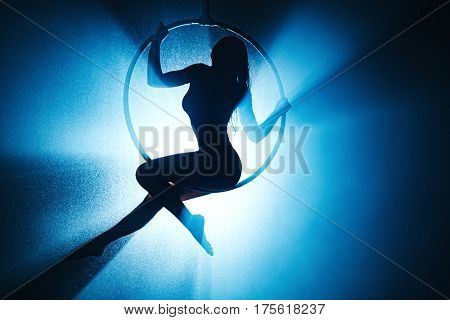 Young sports woman silhouette on ring. With water, smoke and blue light from back.
