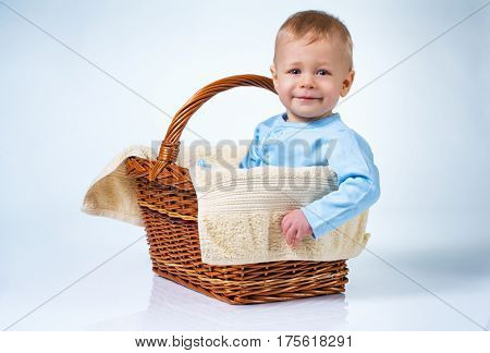 Eight month baby sitting in basket on white and blue background with reflection