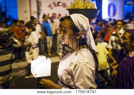Leon Nicaragua - April 15 2014: Girl holding a candle at night in a procession in the streets of the city of Leon in Nicaragua during the Easter celebrations