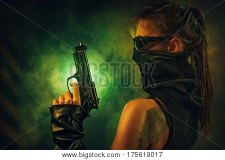 Dangerous woman fighter with gun and scarf in dark interior with smoke. Tattoo on body.