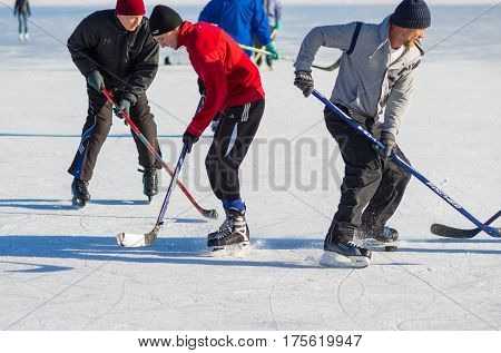 Dnepr Ukraine - January 22 2017: Mature men fighting for the pack while playing hockey on a frozen river Dnepr in Ukraine