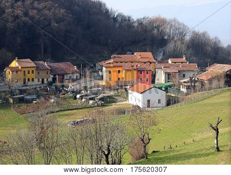 small Italian village with a few houses amid the hills in spring