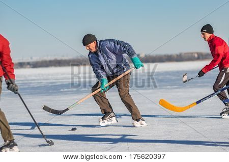 Dnepr Ukraine - January 22, 2017: Mature man leading pack while playing hockey on a frozen river Dnepr in Ukraine
