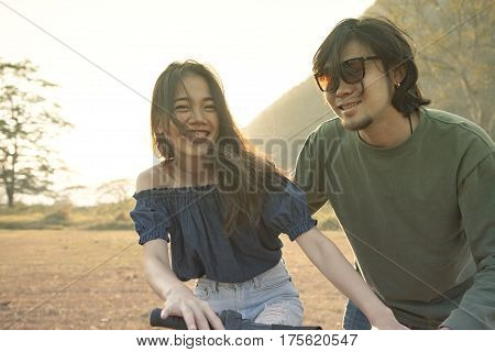 couples of younger asian man and woman practice to riding bicycle in natural field relaxing emotion