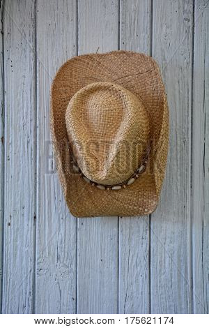 Cowboy care from straw with mussels hangs in the middle   on old white wooden wall