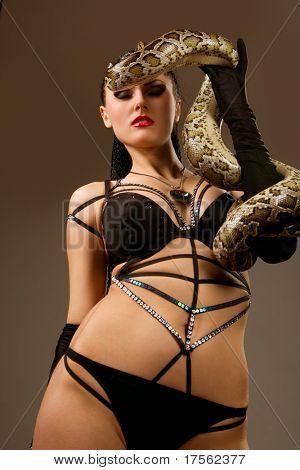 Gorgeous brunette holding boa constrictor