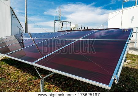 Solar Panels In Power Station Against Wind Turbines Background - Concept Of Sustainable Resources