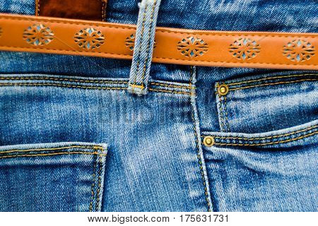 Detail of jeans trousers with brown leather belt close-up. Pockets pants belt loops thick stitches. Elements of denim pants background
