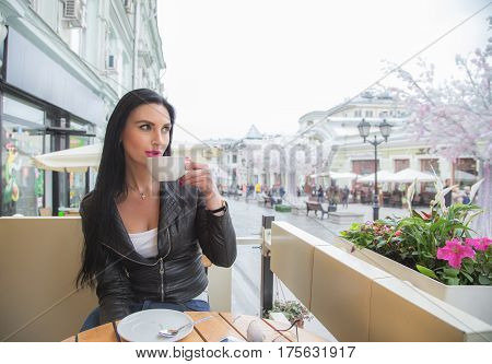 Brunette woman outdoors with a cup of cofee