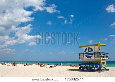 MIAMI BEACH FLORIDA - FEBRUARY 15 2017: Tourists sunbath on Miami Beach Florida USA next to a colorfully painted lifeguard station on February 15 2017.