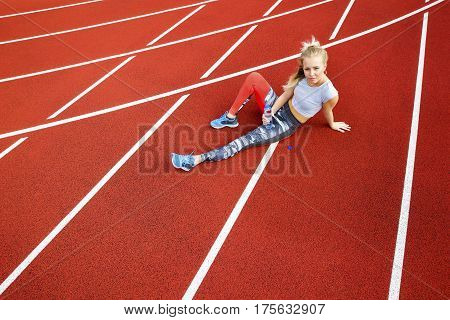 High angle view of sporty young woman with water bottle sitting on running tracks