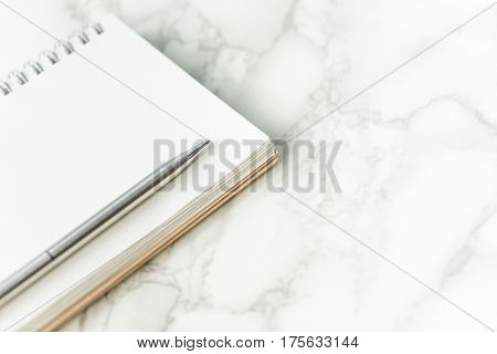Silver metal pen on blank notebook page on marble desk with copy space