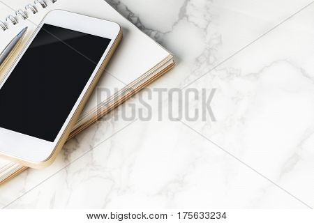 Blank smart phone screen with blank notebook on marble desk with copy space