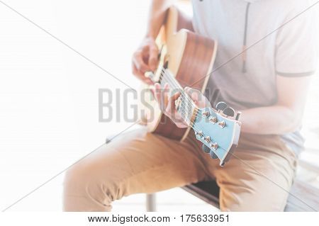 A man plays the guitar outdoors. Street concert. Open air concert. Outdoor entertainment in summer. The concept of life style. Hipster style.