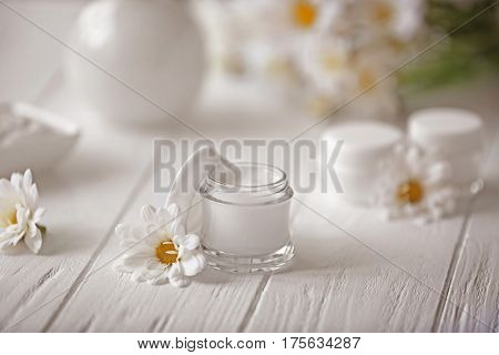 Spa concept. Nourishing cream and daisy flowers on white wooden table
