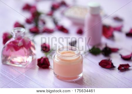 Spa concept. Aroma oil, nourishing cream and flowers on white wooden background