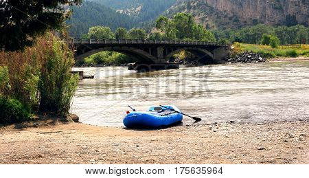 Blue inflatable raft sits on beach of access site at Carter's Bridge near Livingston Montana. Carter's Bridge is listed on National Register of Historic Places.