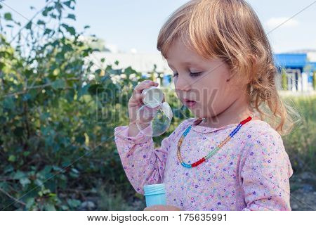 A curly little girl blowing soap bubbles. Concept of children's entertainment outdoors.