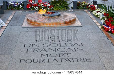 Unknown Soldier memorial flame under Arc de Triomphe in Paris France since 1921. Text translation: a french soldier death for the nation