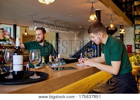 The barman barista  is working at  bar. The waiter writes order in a notepad.
