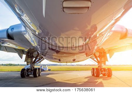 Large modern airplane view from bottom to bottom and landing gear light sun.