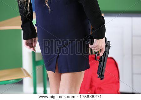 Teenage girl with gun in classroom