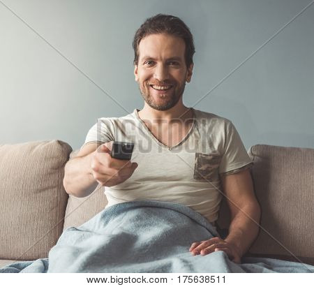 Handsome man is holding a remote control and smiling while watching TV at home